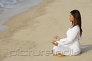PictureIndia - woman practicing yoga at the beach