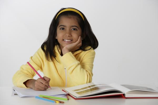 PictureIndia - Girl working with color pencils and book