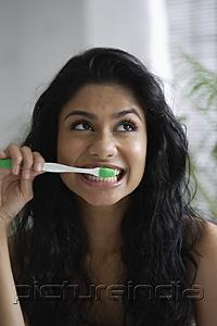 PictureIndia - Head shot of Indian woman brushing her teeth and looking up