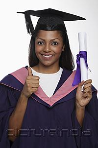 PictureIndia - Young woman wearing cap and gown and holding diploma giving thumbs up sign