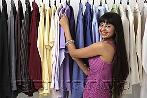 PictureIndia - woman looking at rack of clothes and smiling