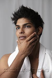 PictureIndia - Young man feeling his chin with towel around his neck