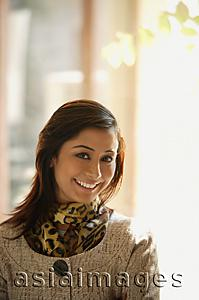 Asia Images Group - woman with jacket and scarf, smiling at camera