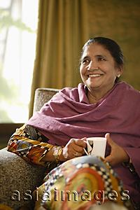 Asia Images Group - older woman sitting on couch, holding tea