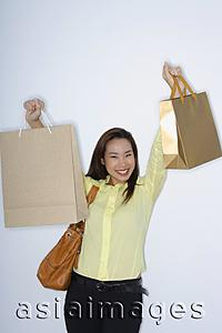 Asia Images Group - woman holding up shopping bags