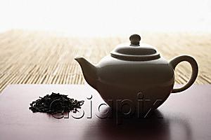 AsiaPix - tea leaves in a pile and teapot on bamboo mat closeup
