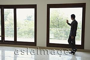 Asia Images Group - businessman next to window