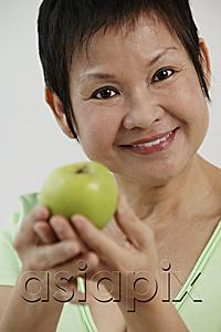AsiaPix - Mature Chinese woman holding green apple and smiling