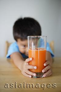 Asia Images Group - Little boy looking at glass of juice