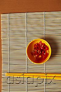 AsiaPix - Small bowl of red chillies and chopsticks.