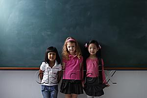 AsiaPix - three young girls standing in front of chalk board