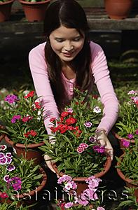 Asia Images Group - Young woman picking up a flower pot
