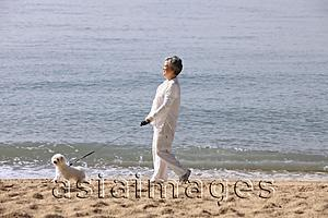 Asia Images Group - Older woman walking dog.