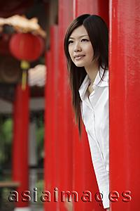Asia Images Group - Young woman looking out from behind red pillars