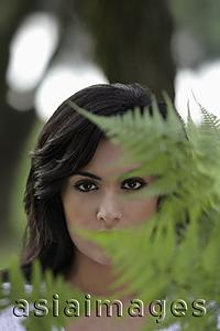 Asia Images Group - Head shot of young woman looking through ferns