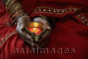 Asia Images Group - Close up of woman wearing red sari and holding lit candle