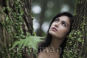 Asia Images Group - Head shot of young woman looking up with tree in foreground