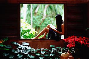 Asia Images Group - Woman sitting on window ledge, reading