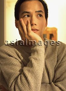 Asia Images Group - Man with thoughtful expression, resting head on hand