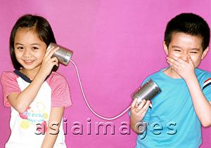 Asia Images Group - Children playing with toy string telephone, purple background.