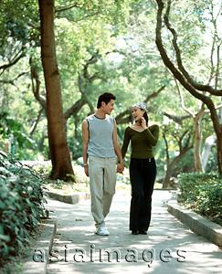 Asia Images Group - Young couple walking down path holding hands, nature in background.