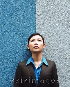 Asia Images Group - Executive woman standing against split colored background, looking up.