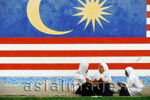 Asia Images Group - Malaysia, Kukup, three Muslim schoolgirls chatting in front of a large Malaysian flag painted on the wall behind them.
