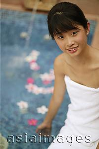 Asia Images Group - Young woman sitting by pool
