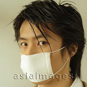 Asia Images Group - Man with a face mask, portrait