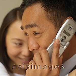 Asia Images Group - Businessman on mobile phone, woman in the background