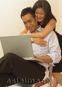 Asia Images Group - Man using laptop, woman hugging him