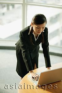 Asia Images Group - Young woman standing, using laptop