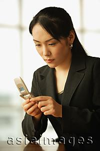 Asia Images Group - Young woman sitting at desk, using mobile phone