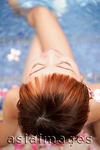 Asia Images Group - Young woman sitting at edge of pool, directly above