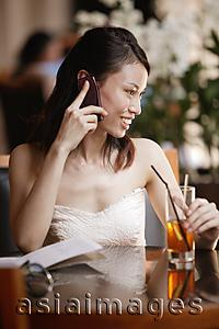 Asia Images Group - Young woman using mobile phone in a cafe