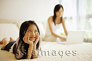 Asia Images Group - Mother and daughter in bedroom, mother using laptop