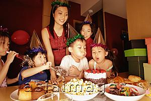Asia Images Group - Young boy blowing out candles on a cake