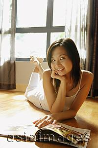Asia Images Group - Young woman lying on floor with magazine, looking at camera