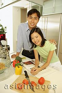 Asia Images Group - Young adults standing in kitchen, side by side, looking at camera