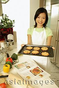 Asia Images Group - Young woman holding out baking tray, looking at camera