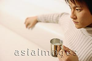 Asia Images Group - Young man sitting, holding coffee mug
