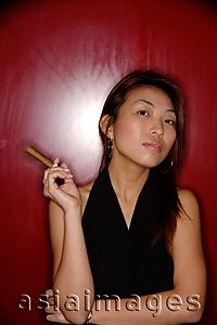 Asia Images Group - Woman with cigar, looking at camera.