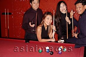 Asia Images Group - Men and women standing around pool table, looking at camera
