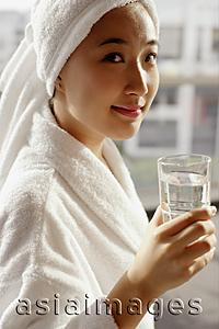 Asia Images Group -  Young woman in robe holding glass of water