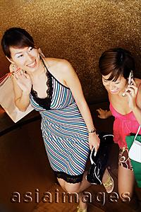Asia Images Group - Two women with shopping bags, climbing stairs