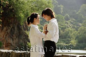 Asia Images Group - Couple holding hands, face to face