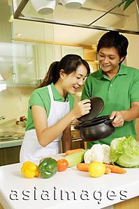 Asia Images Group - Couple in kitchen, woman lifting lid of pot and looking in
