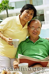 Asia Images Group - Woman holding coffee mug, man sitting down holding newspaper, looking at camera