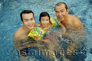 Asia Images Group - Father, grandfather and young girl in a swimming pool, looking at camera