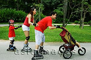 Asia Images Group - Family wearing roller blades, skating all in a row, father pushing stroller
